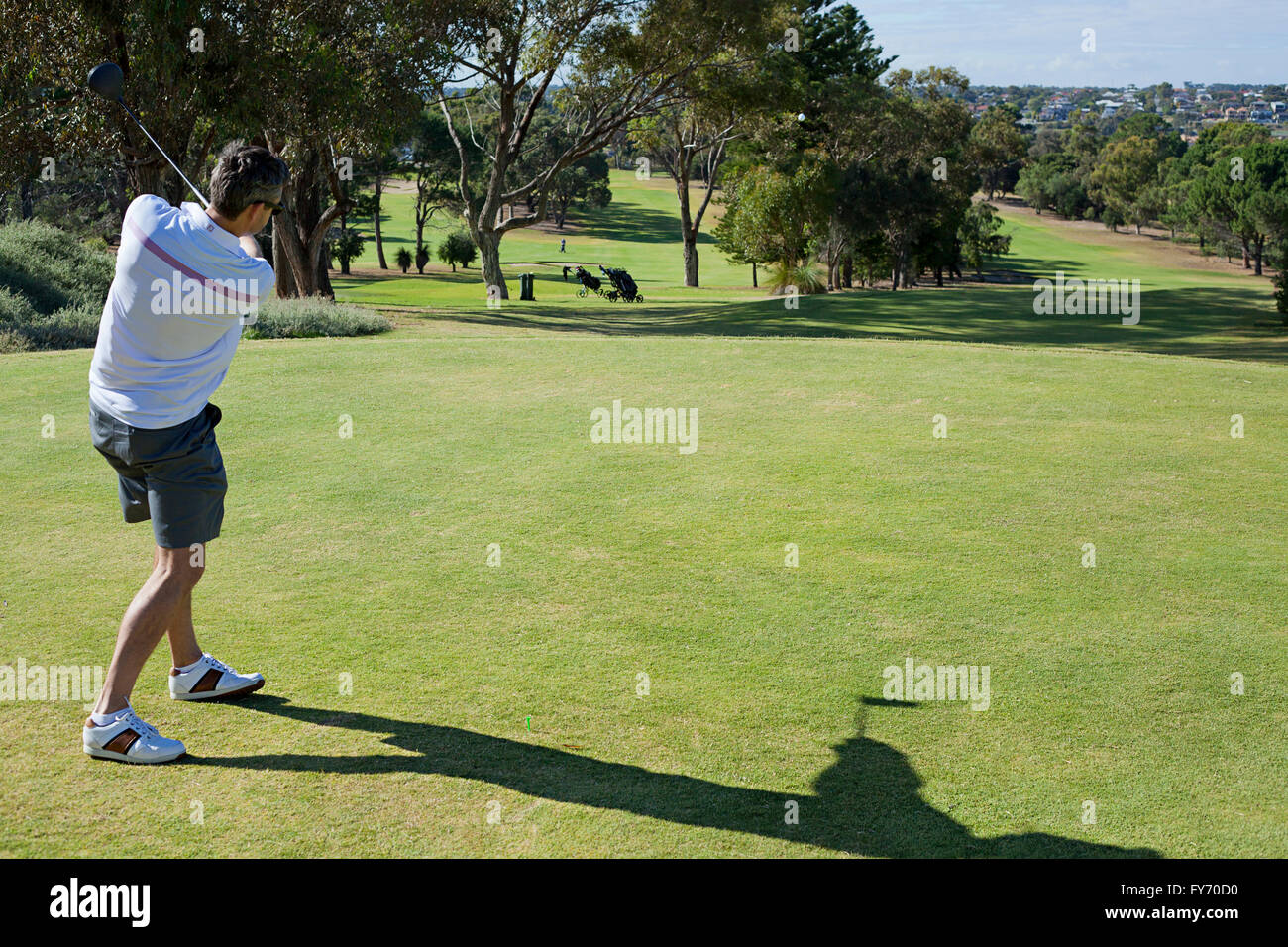 A young golfer in the finishing position, after hitting a tee shot - Stock Image