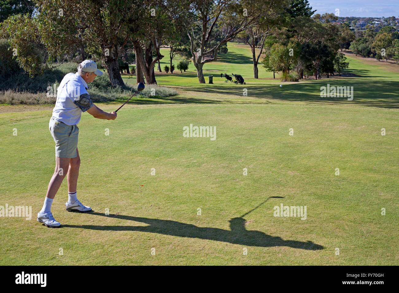 A golfer after hitting a tee shot - Stock Image