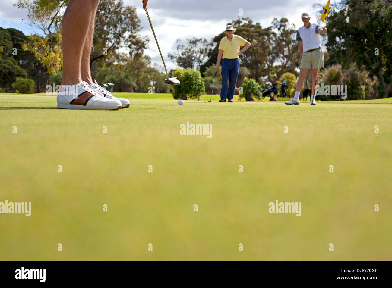 Low angle photo of man putting on golf green with two fellow golfers looking on. - Stock Image