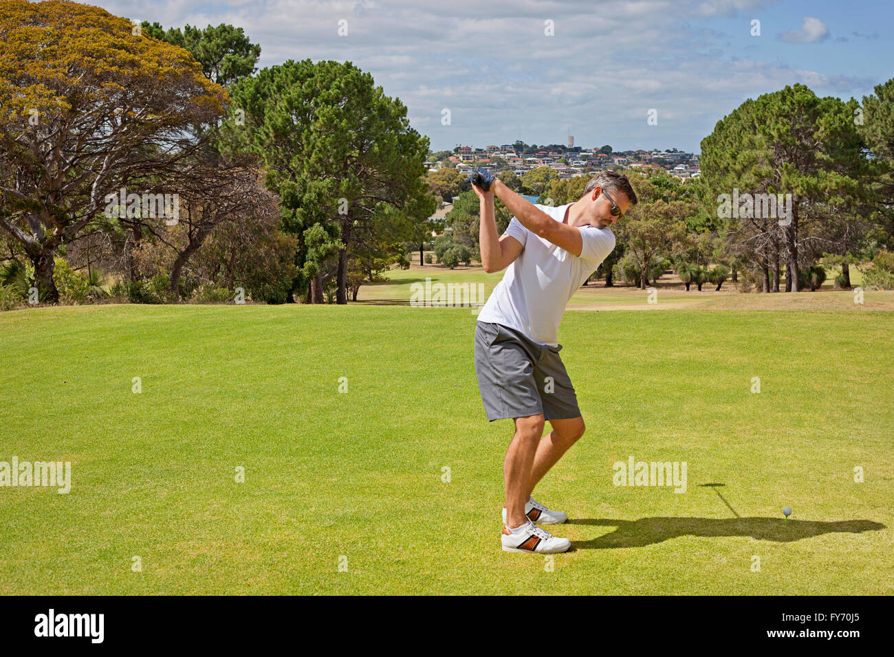 A golfer in the starting position before hitting a tee shot - Stock Image