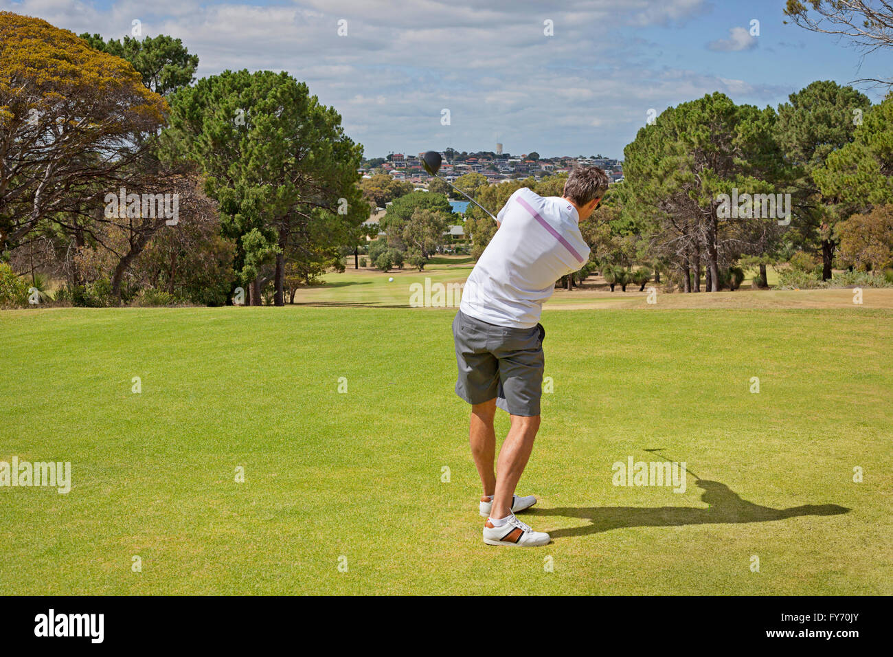 A golfer shortly after hitting a tee shot - Stock Image