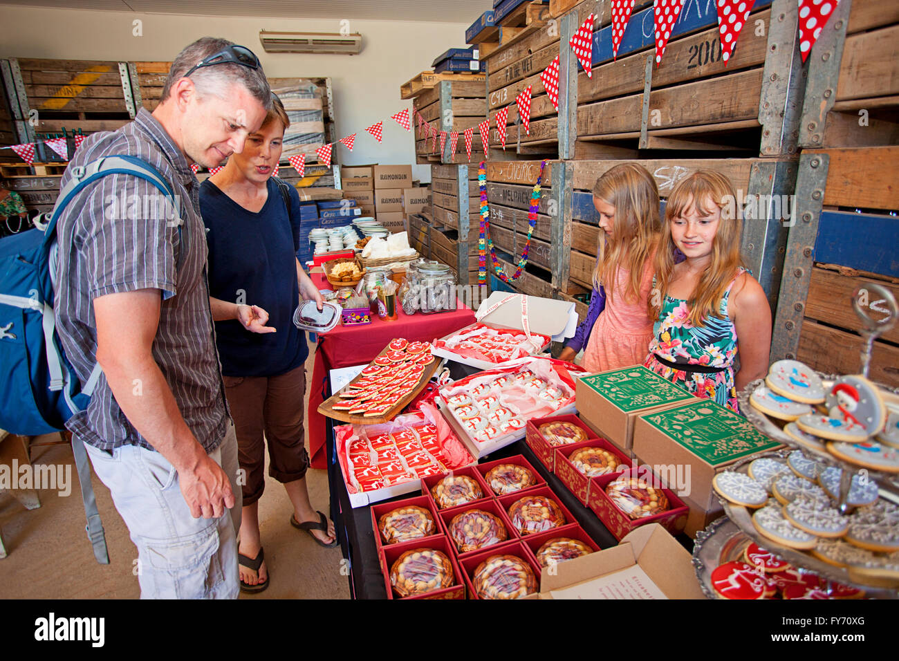Husband and wife peruse wares at a food market - Stock Image