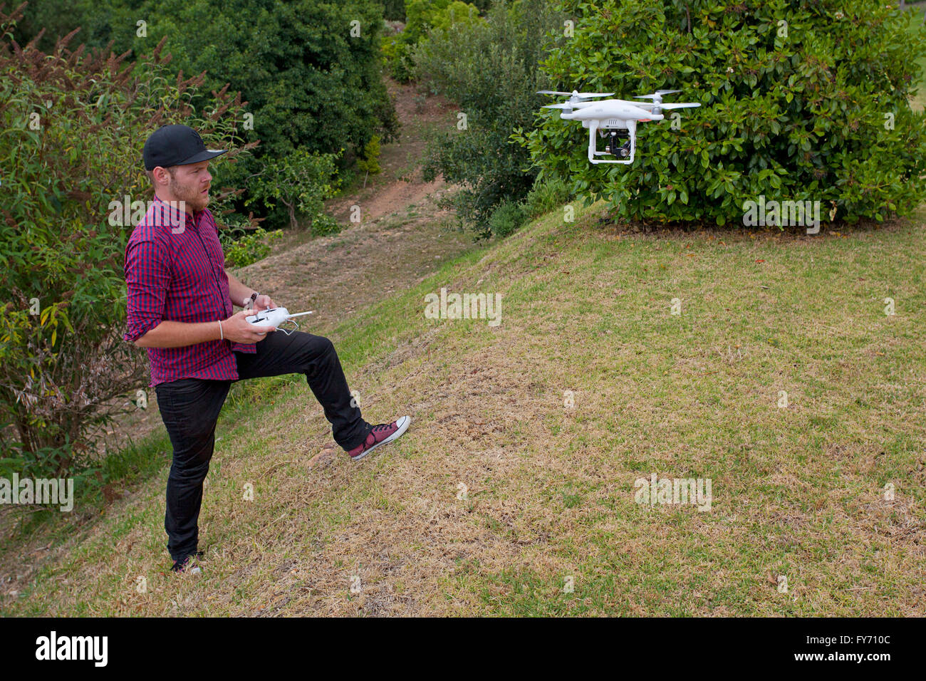 Pilot controlling a Phantom drone for commercial aerial photography - Stock Image