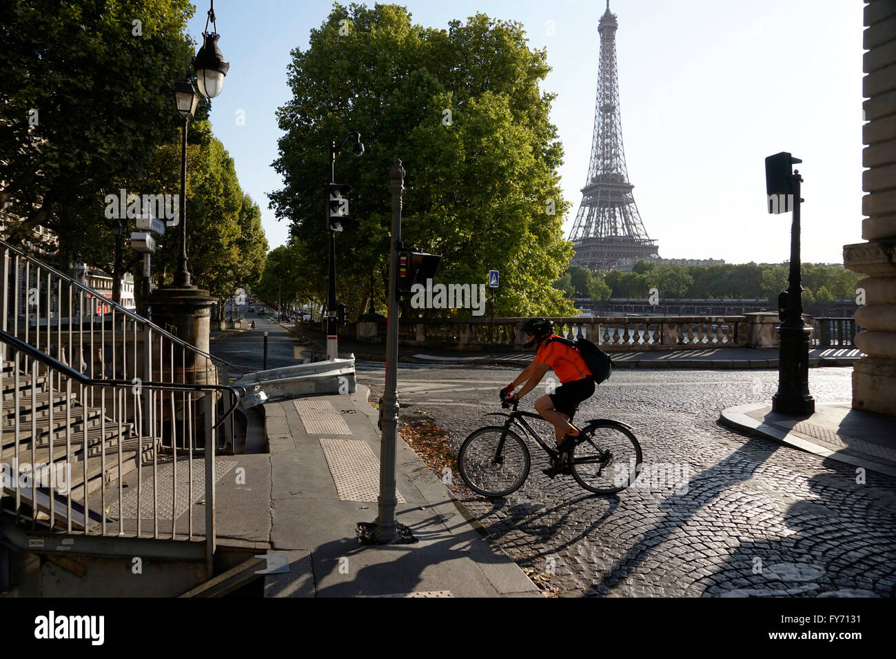 A man riding bicycle on the end of Pont Bir-Hakeim Bridge with Eiffel Tower in the background, Paris, France Stock Photo
