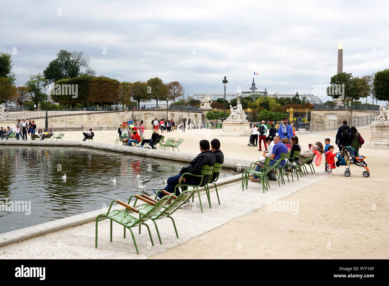 Visitors relaxing by the Grand Bassin Octagonal inTuileries Garden, Jardin des Tuileries,Paris. France - Stock Image