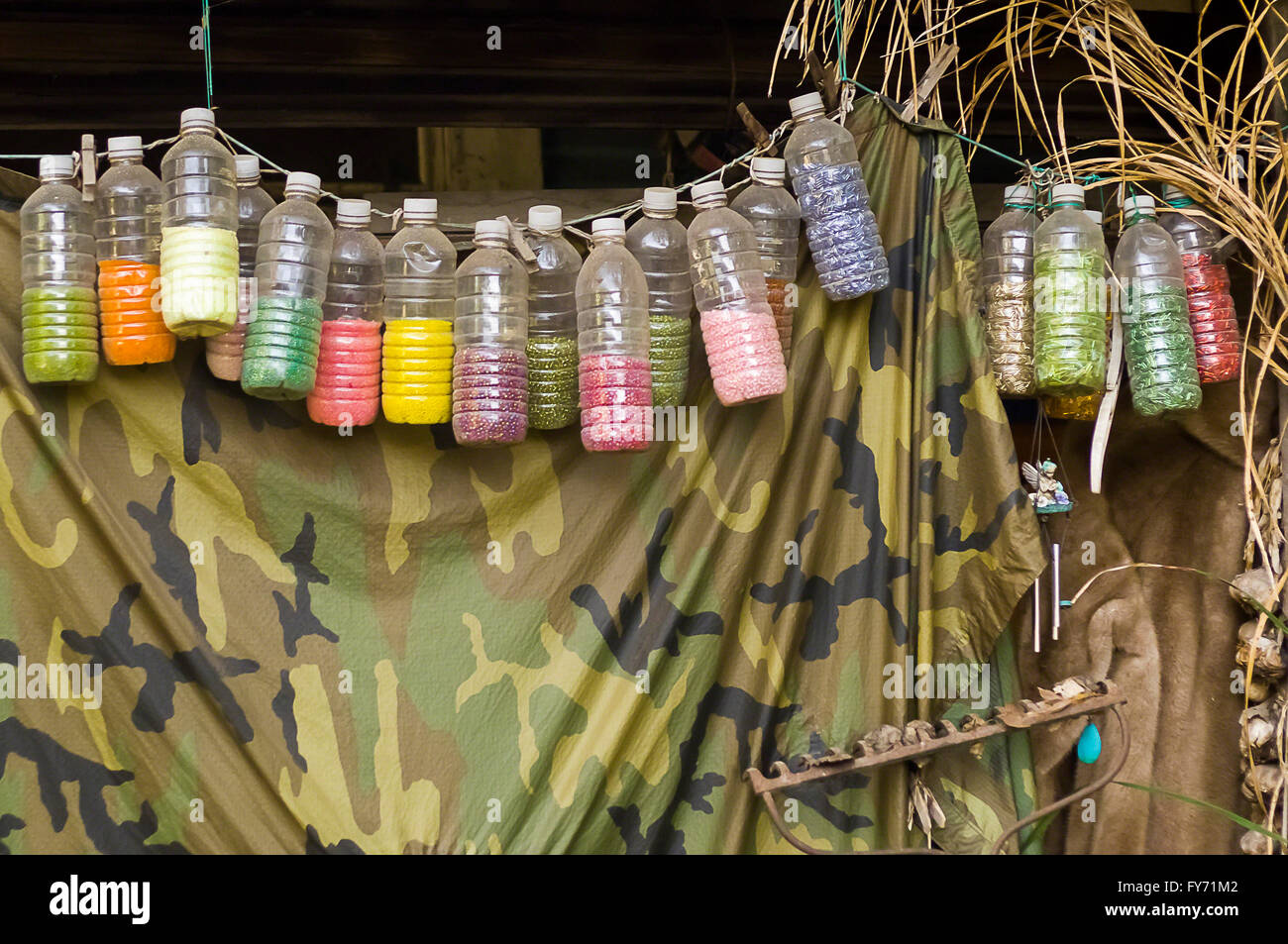 Colorful water bottles filled with beads hang from a porch - Stock Image
