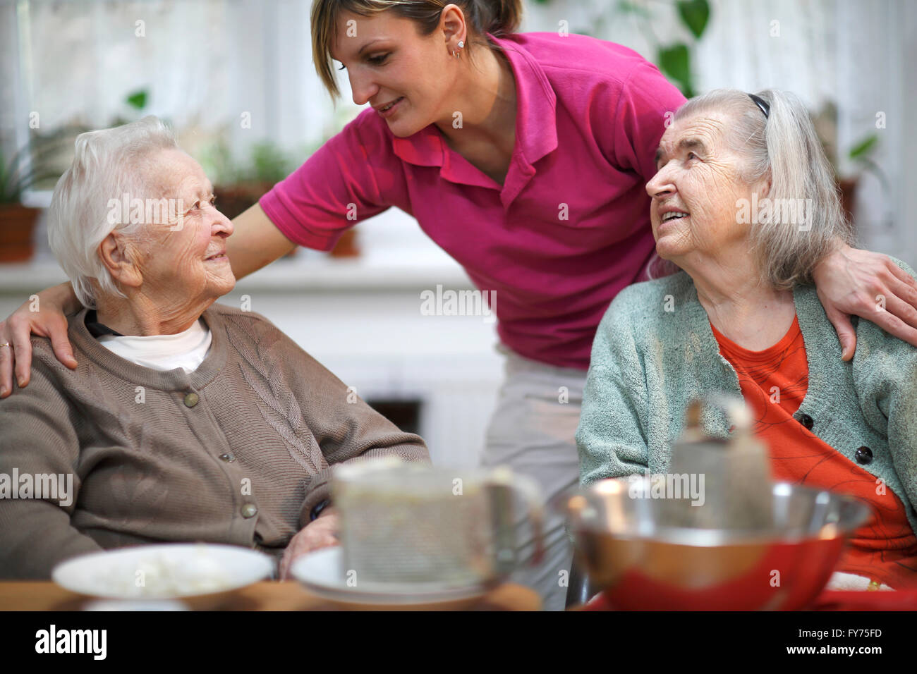 Two elderly women, 78 years and 88 years, and a carer for the elderly, 31 years, leisure activities in a nursing - Stock Image