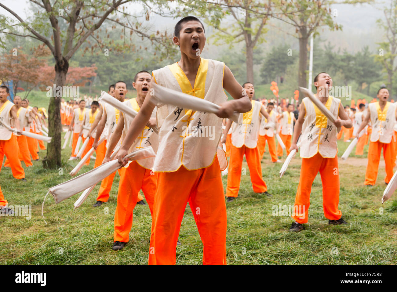 Students of Shaolin martial arts school conditioning their body with metal bars at the opening ceremony of Zhengzhou - Stock Image