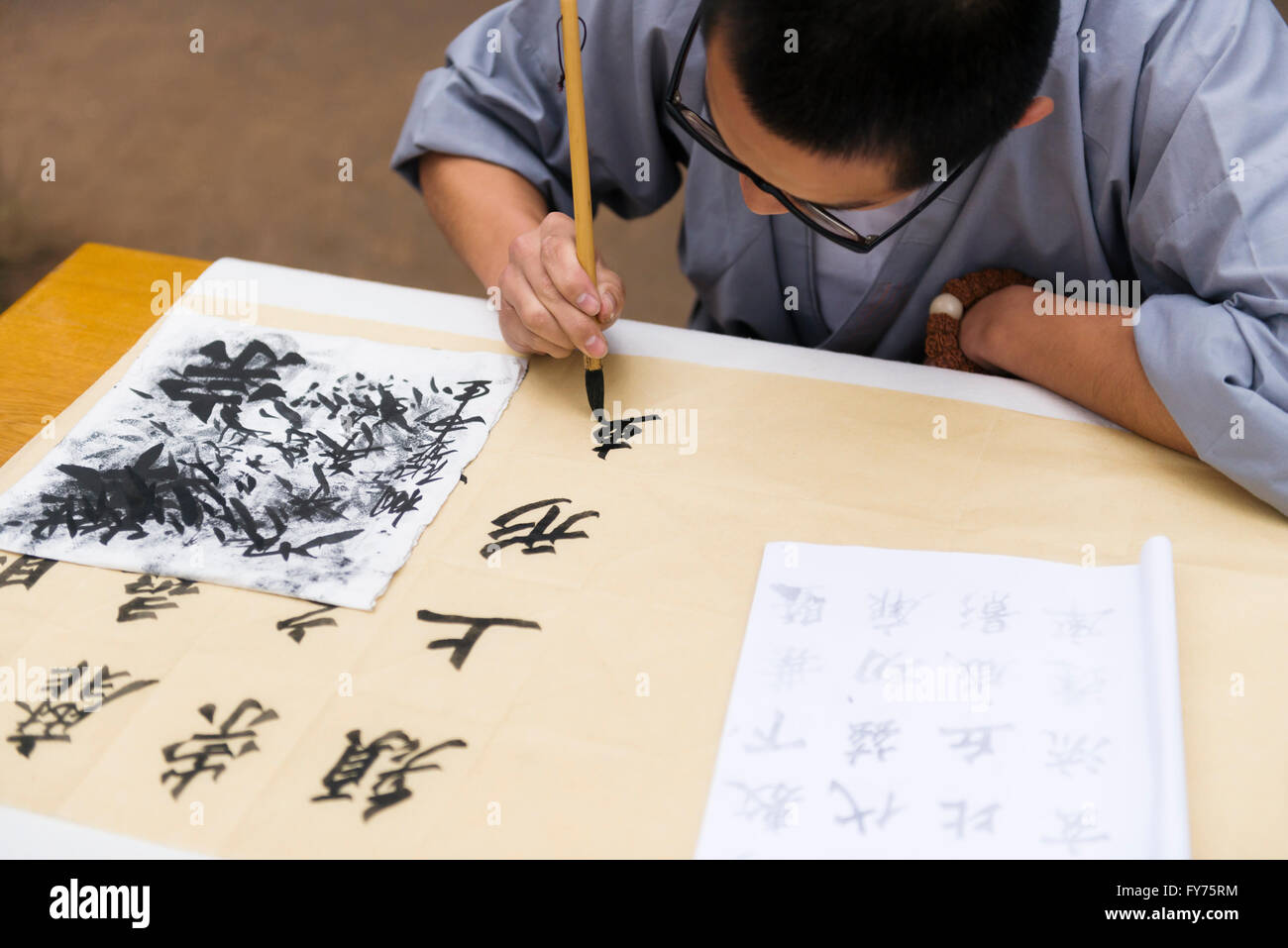 Student of a Shaolin martial arts school practices Chinese calligraphy, Dengfeng, Zhengzhou, Henan, China - Stock Image