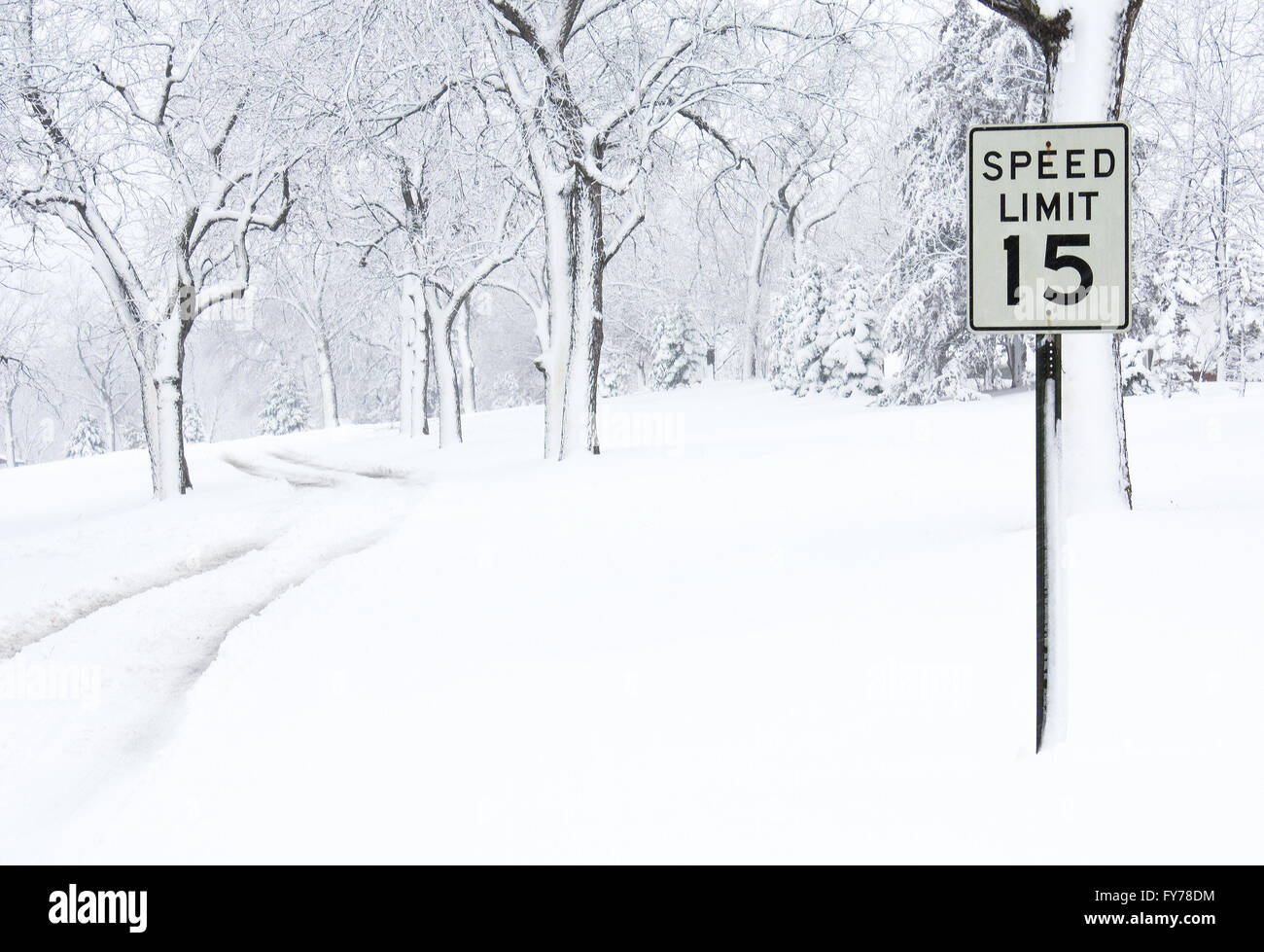 A speed limit sign on a snow covered road - Stock Image