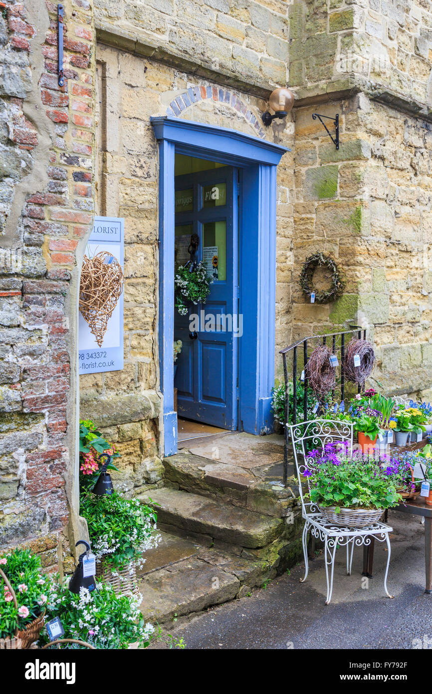 Pretty florist shop in a traditional stone building in Petworth, West Sussex with stone steps and display of flowers - Stock Image