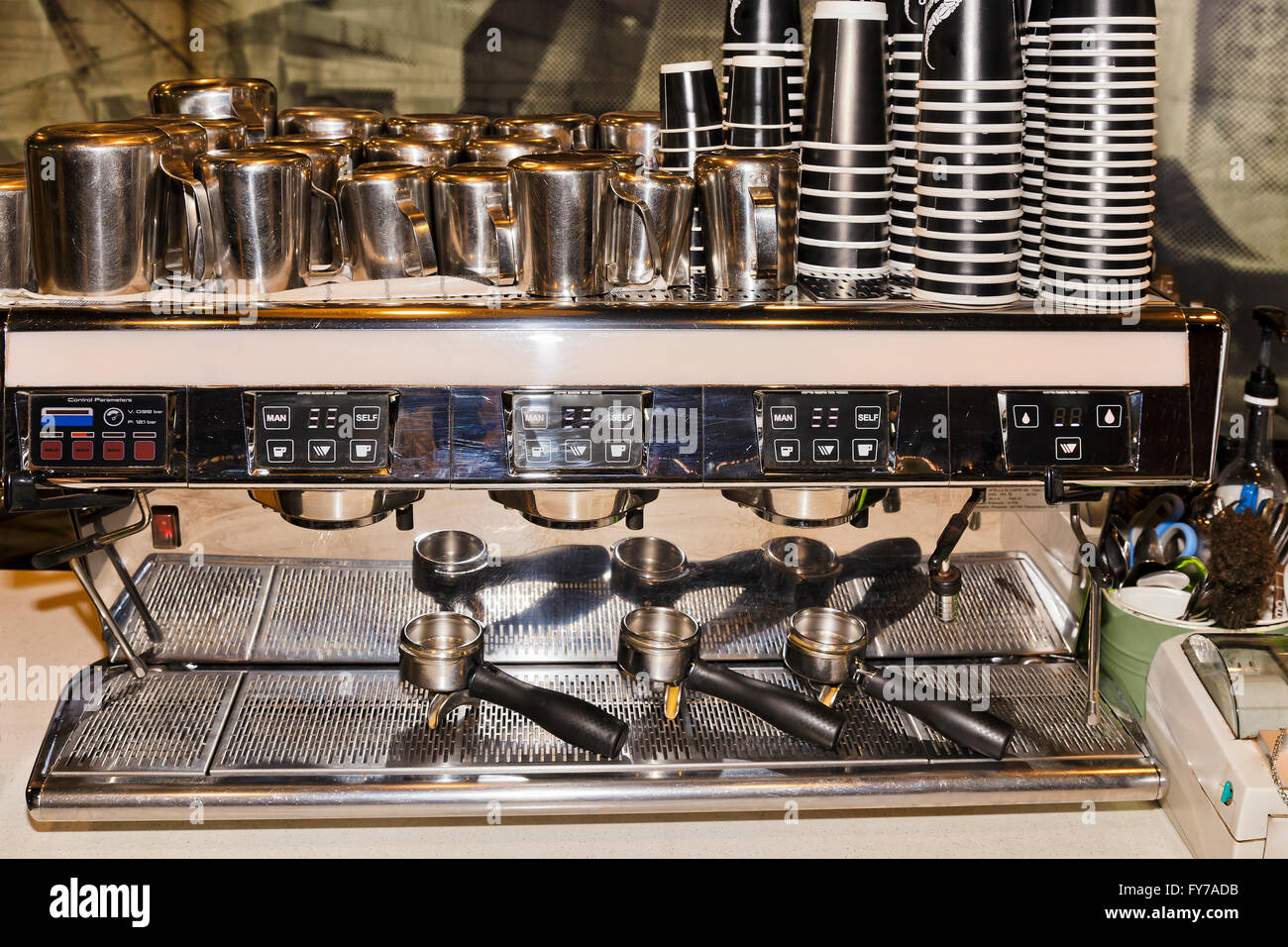 Front of industrial barista coffee machine with portafilters , cups, pots and handlers ready to make ground coffee. - Stock Image