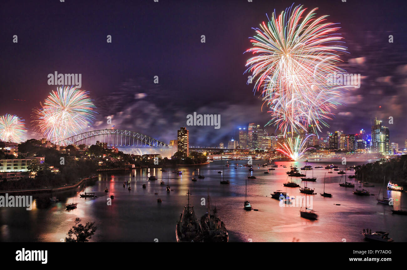 Sydney New Year eve fireworks over Harbour with bridge and city CBD buildings reflecting colourful fire balls in - Stock Image