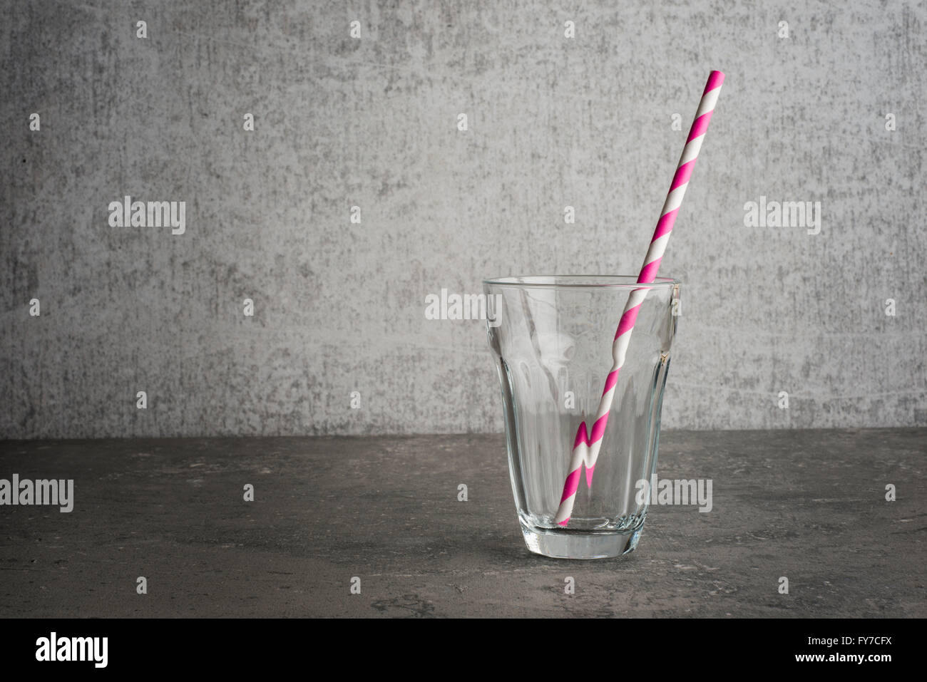 Empty glass with drinking straw studio still life The straw is striped  the glass is st ing on a stone table Copy - Stock Image