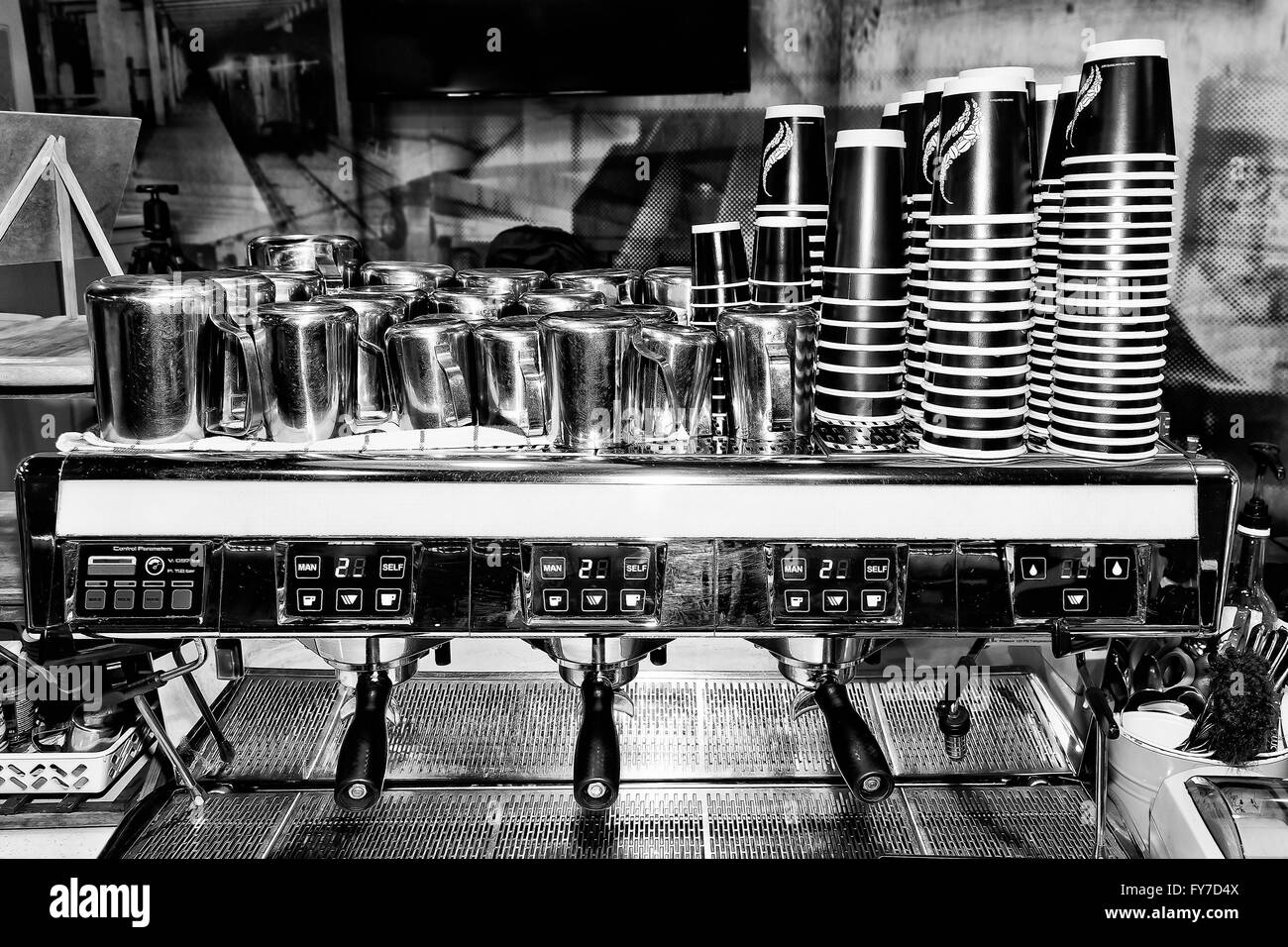 Black white image of industrial large scale barista coffee machine in a cafe ready to serve customers with piles - Stock Image