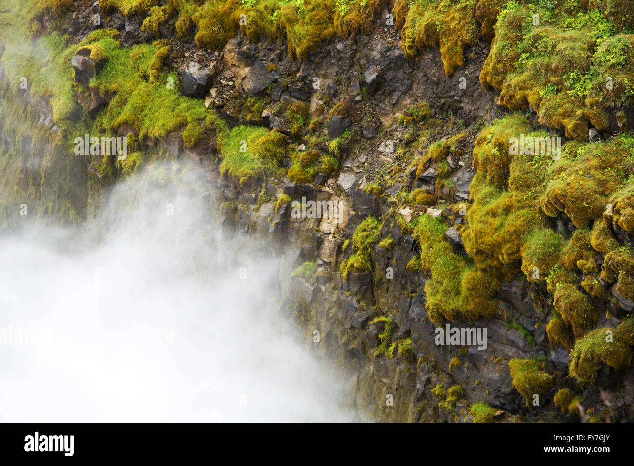 Rocks with green grass and falling water vapor - Stock Image