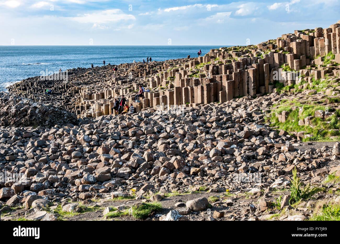 Giants Causeway. Tourists visiting unique geological hexagonal formations of volcanic basalt rocks on Atlantic coast - Stock Image