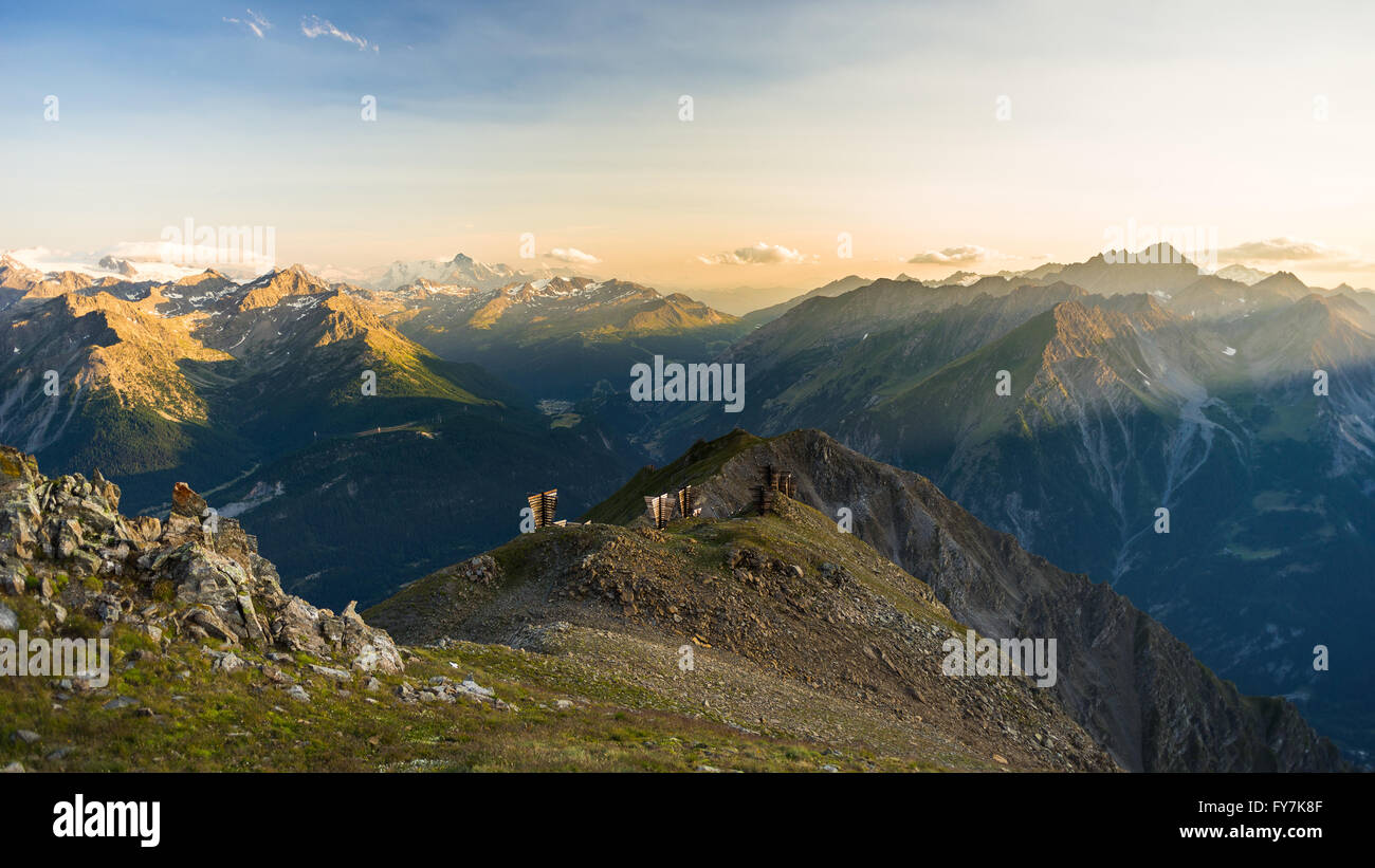 Last soft sunlight over rocky mountain peaks, ridges and valleys of the Alps at sunrise. Extreme terrain landscape - Stock Image