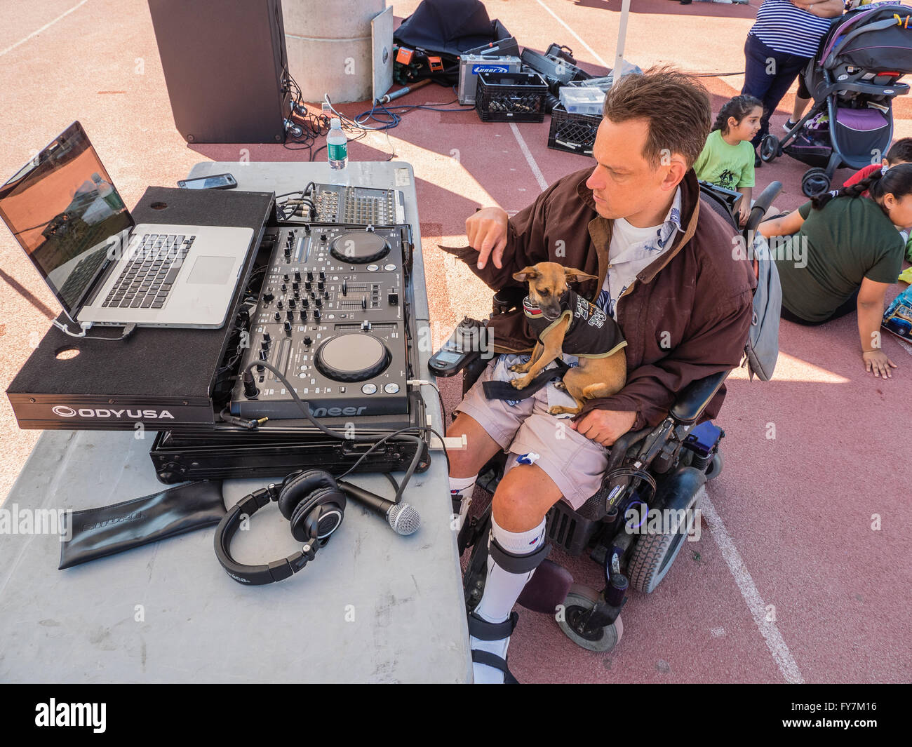 A wheelchair bound disabled middle-aged man works his sound equipment as he works as a disc jockey at the Special - Stock Image