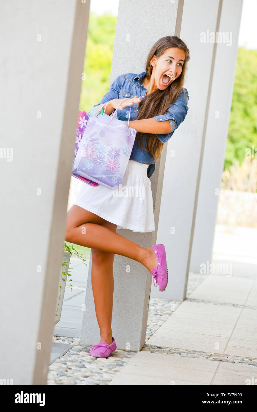 Young female shopper with paper bags is wondering attractive good-looking full-length fun legs giggling giggle - Stock Image