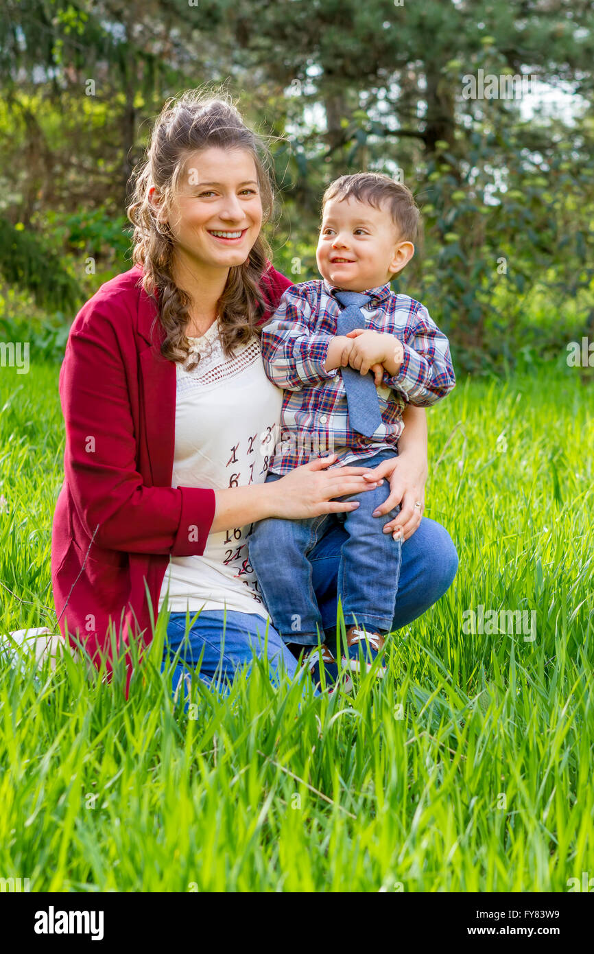 Beautiful pregnant woman smiling outdoor with her baby boy. - Stock Image