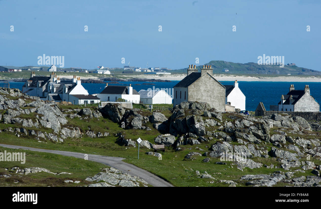 Tiree Inner Hebrides, rocky shoreline and the village of Mannal Isle of Tiree, Inner Hebrides, Scotland GB - Stock Image