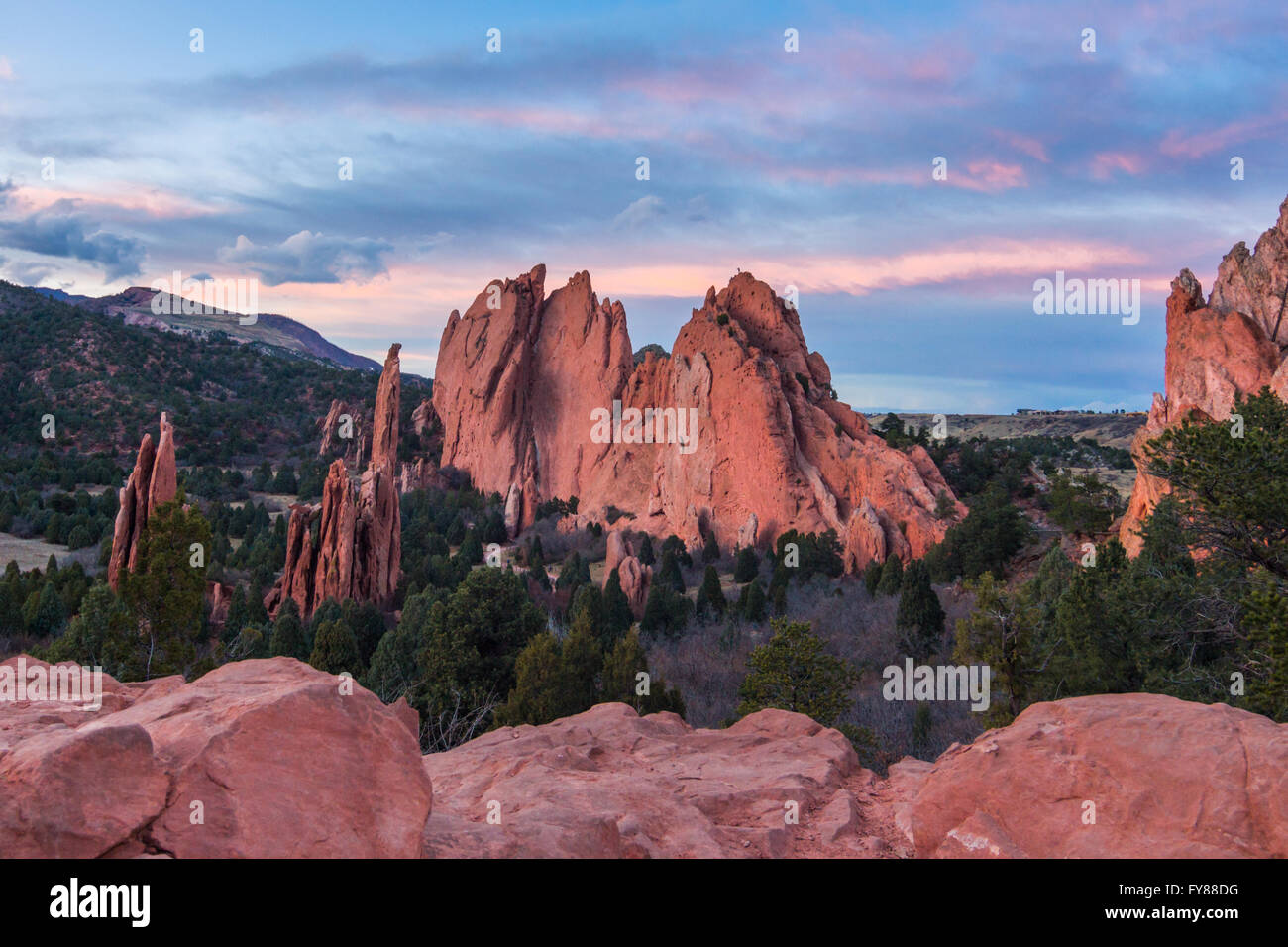 A pink and blue sunset stretches over towering red rock formations in Garden of the Gods park near Colorado Springs, - Stock Image