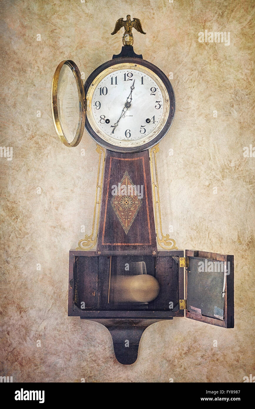 Antique 1930s Sessions Banjo Clock on weathered wall with open face and so pendulum - Stock Image