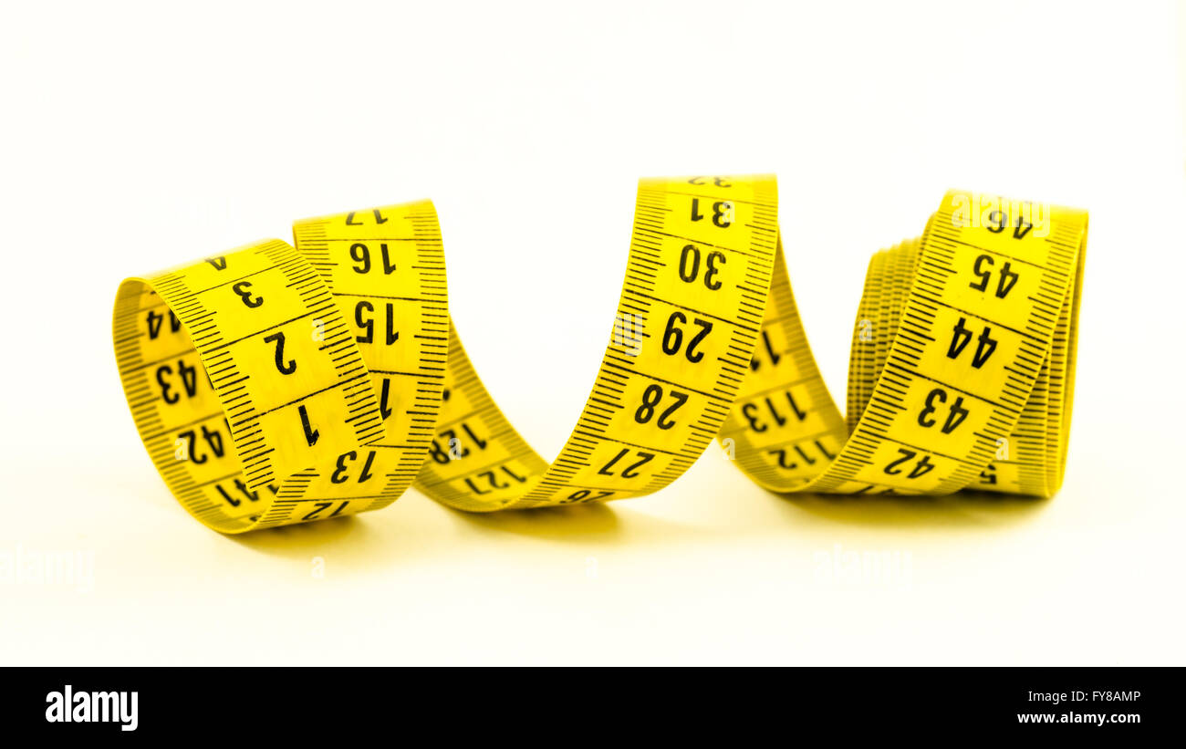 still life with a yellow tape measure and a pencil, over white - Stock Image
