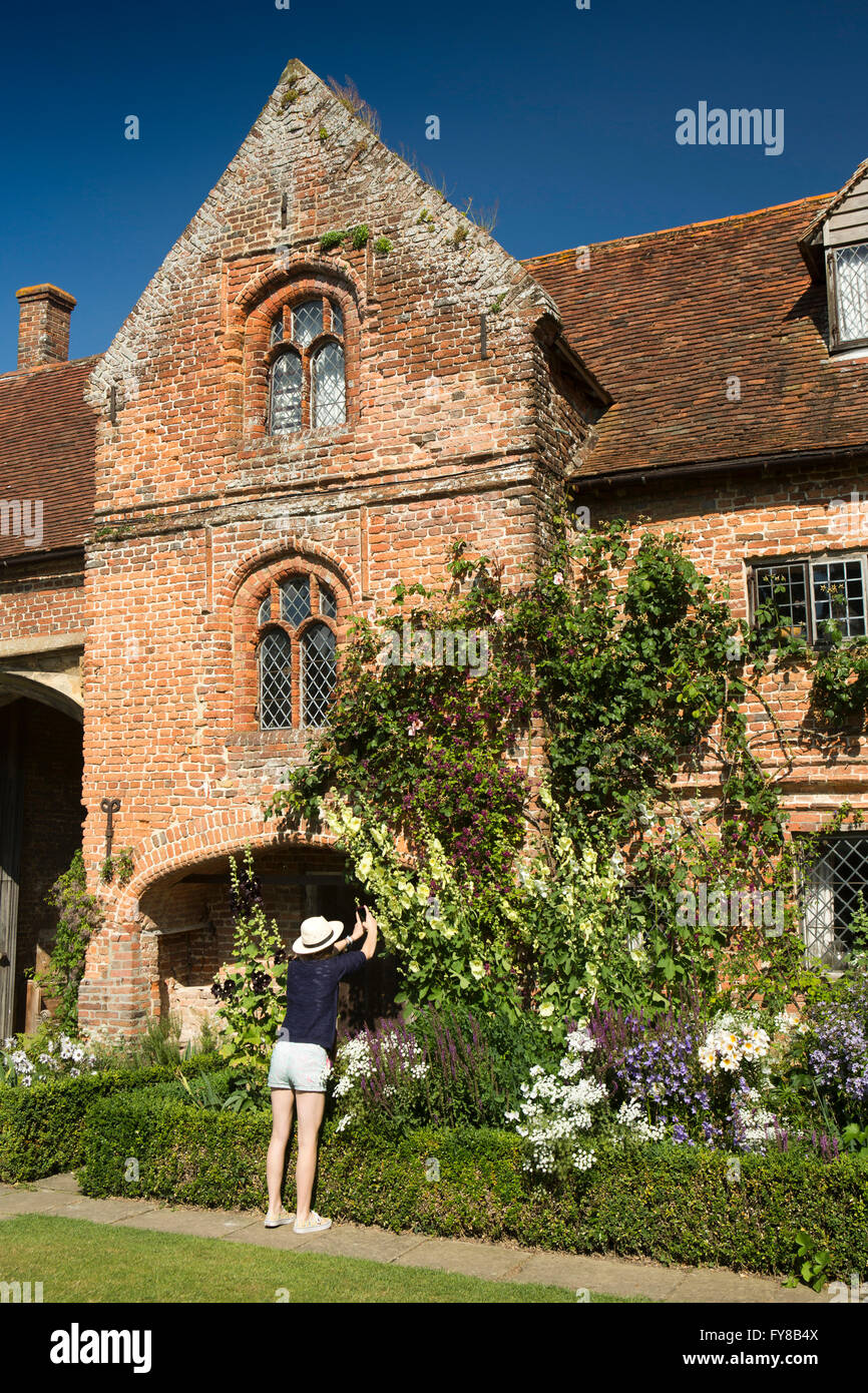 UK, Kent, Sissinghurst Castle, home to Vita Sackville West and Harold Nicolson in 1930s, visitor photographing flowers - Stock Image