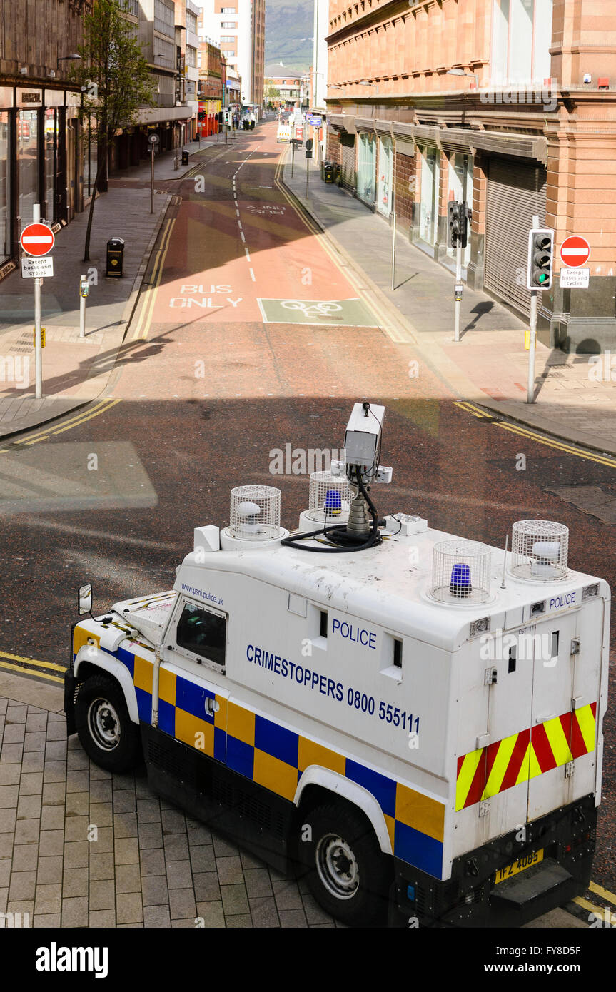 A PSNI armoured Landrover, fitted with a high-power CCTV camera, surveys a street for signs of trouble. - Stock Image