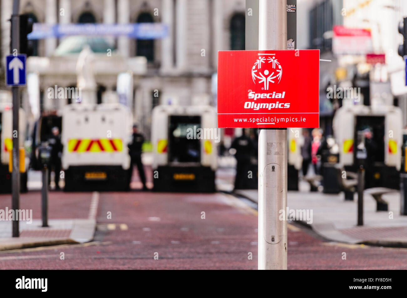 PSNI police officers with armoured landrovers block off Donegal Place in Belfast, where a Special Olympics sign - Stock Image
