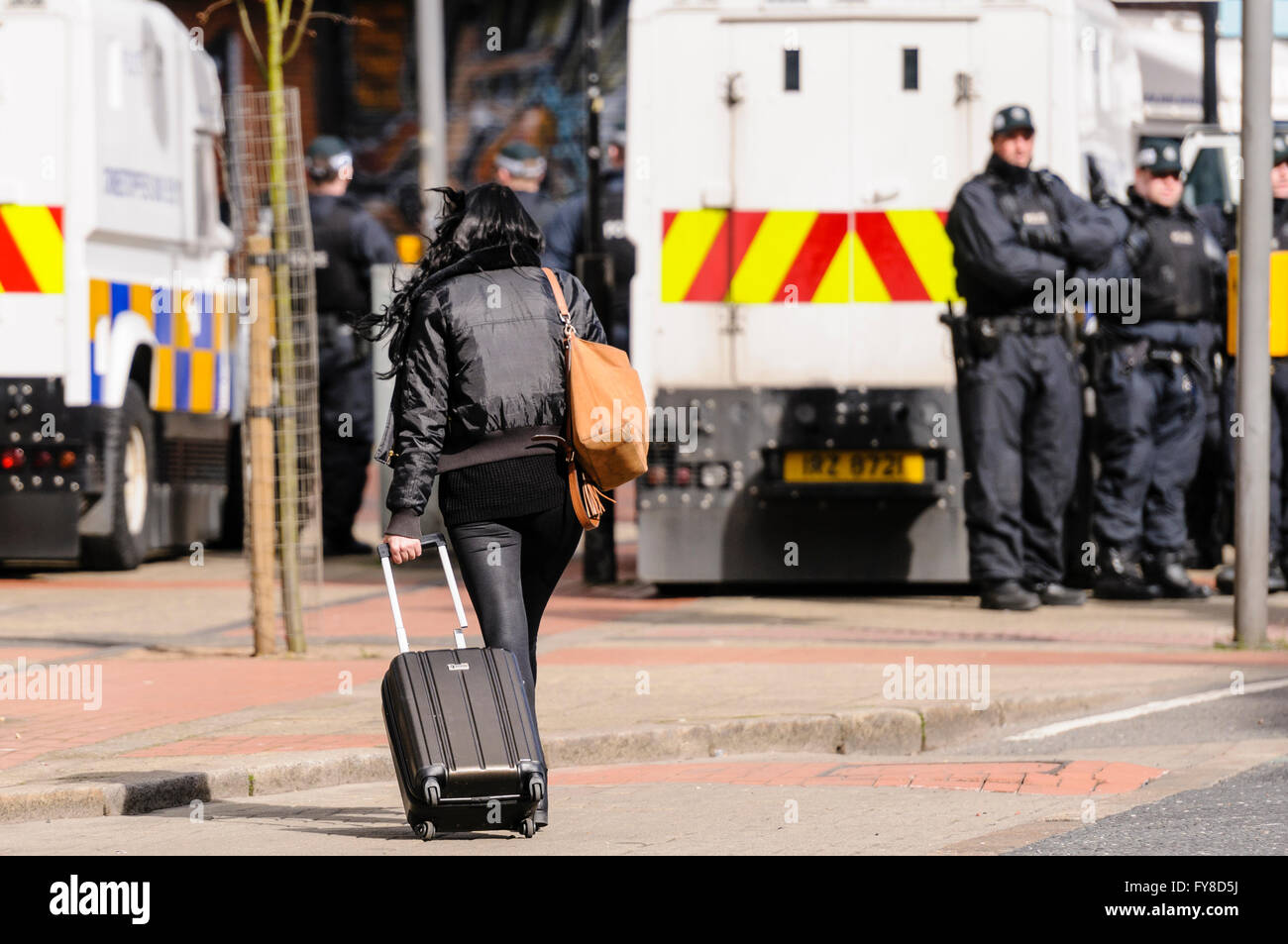 A woman wheels a suitcase towards a line of PSNI police officers in Belfast. - Stock Image