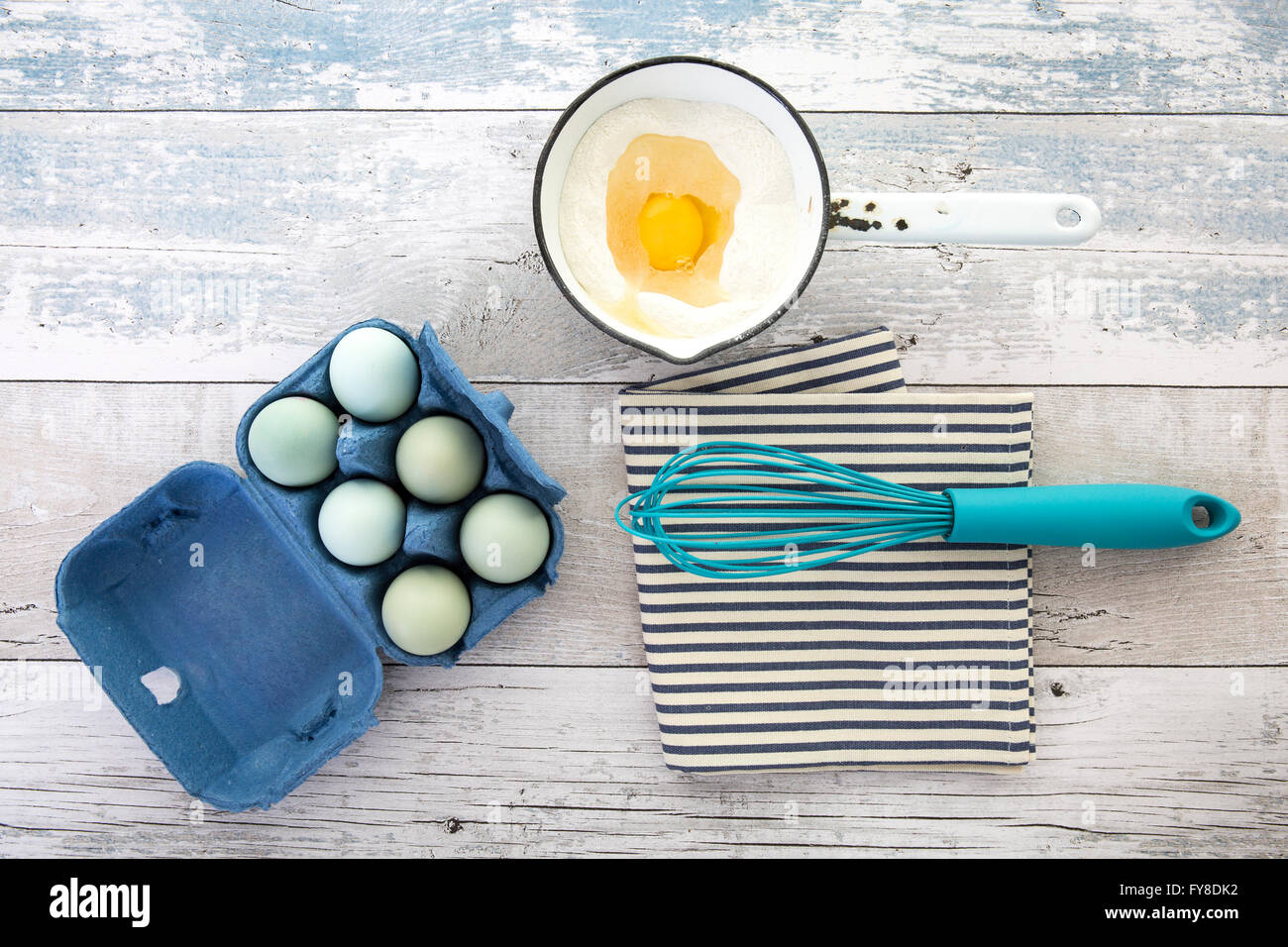 Eggs in a box with a whisk on a rustic wood table top shot from above - Stock Image
