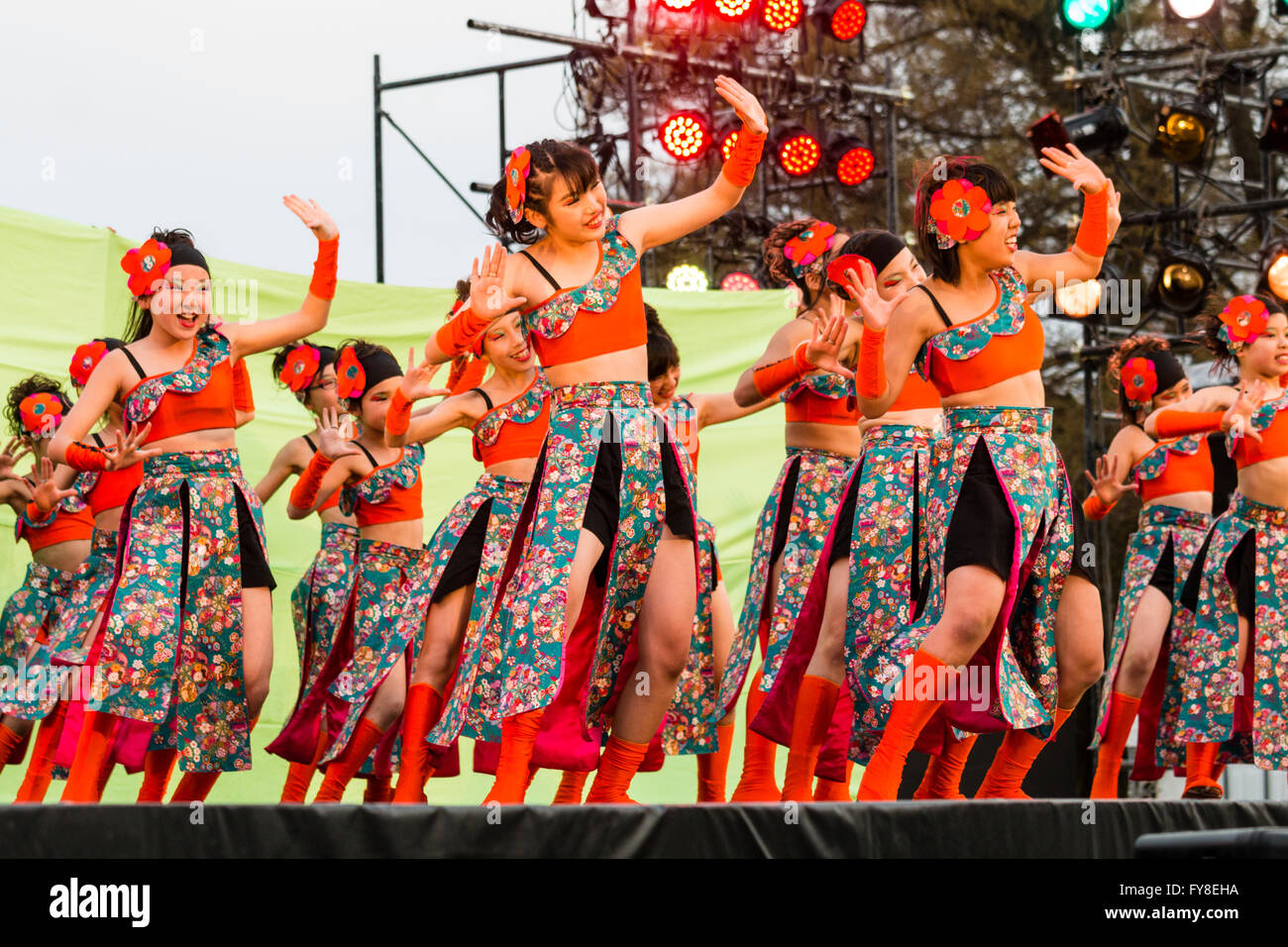 Young Japanese teenage and child dance troupe wearing orange cropped tops dancing on stage as part of the Yosakoi - Stock Image