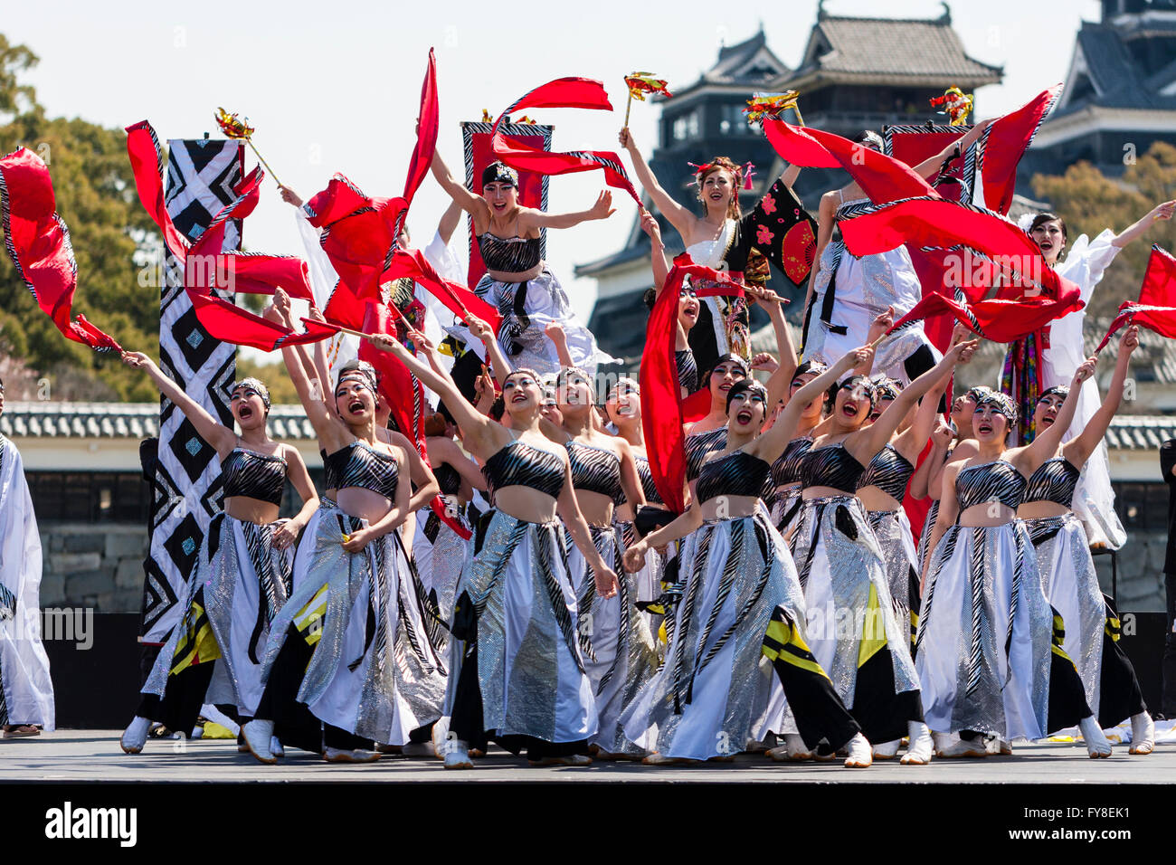 Japanese yosakoi festival, young women dance troupe gathered together on stage , arms outstretched and holding red - Stock Image
