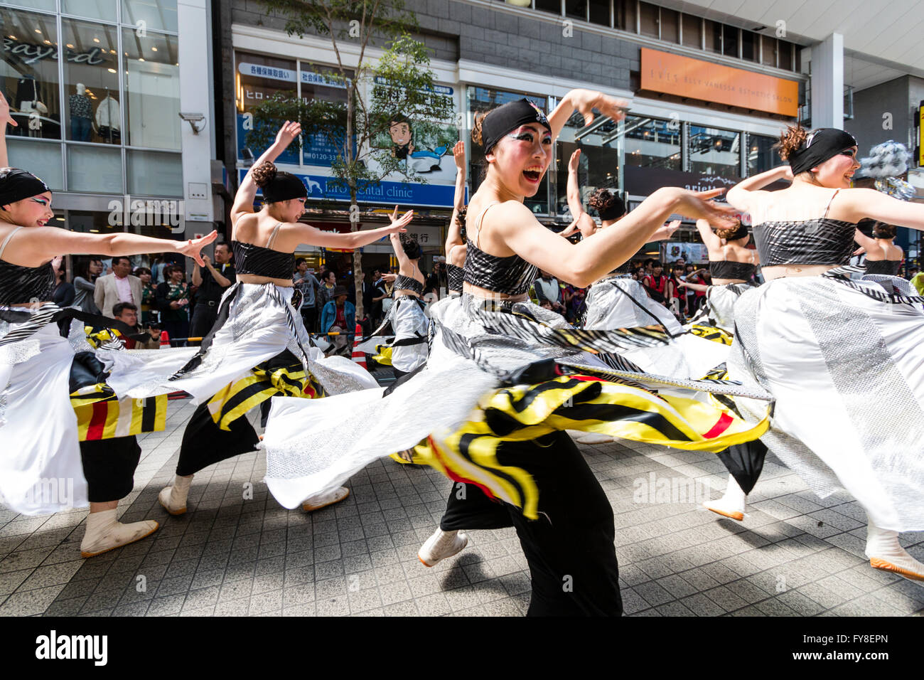 Japanese young women dance team in black and white costume formation dancing and skirts swirling, in shopping arcade - Stock Image