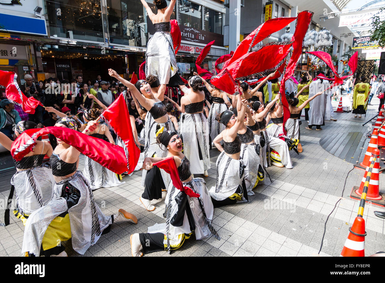 Japanese young women dance team in black and white costume formation dancing and swirling red streamers in shopping - Stock Image
