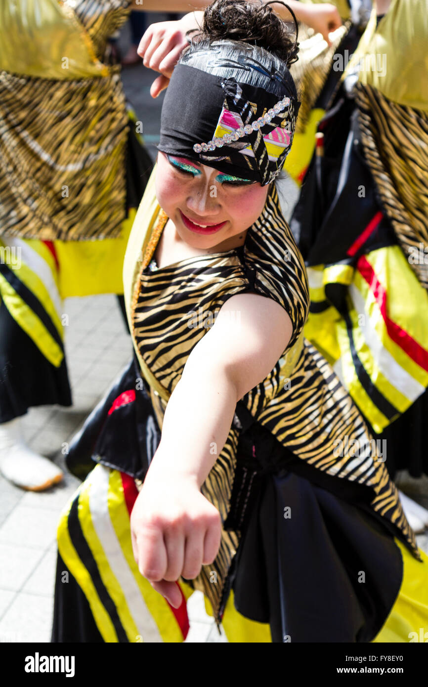 Japanese Yosakoi Dance festival at Kumamoto. Close up, young woman dancer in black and yellow costume, arm outstretched - Stock Image