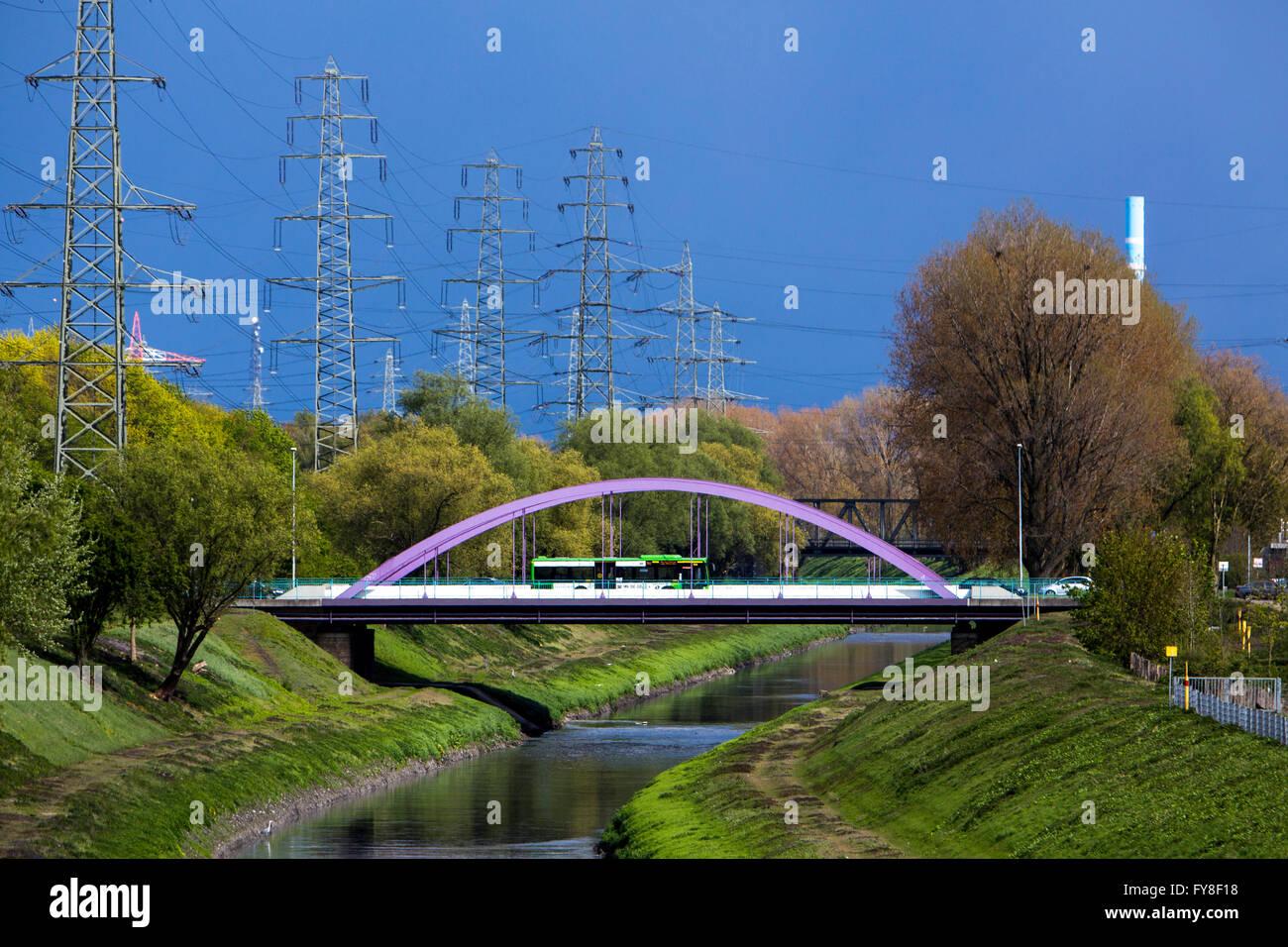 Bridge over river Emscher, in Oberhausen, Germany, dark cloudy sky, high wire electrical power lines, - Stock Image