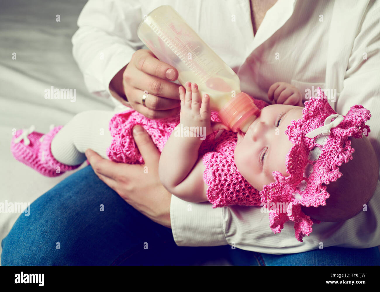 father feeding his four months old baby with milk from the bottle. - Stock Image