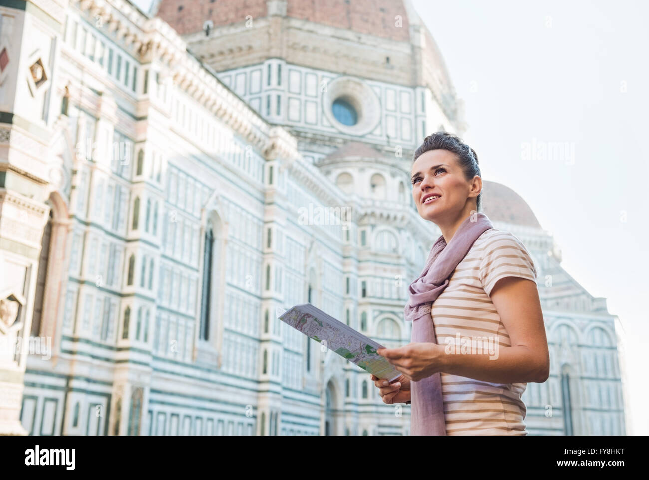 An amble around awe-inspiring Duomo in Florence, Italy. Happy woman with tourist map looking into the distance - Stock Image