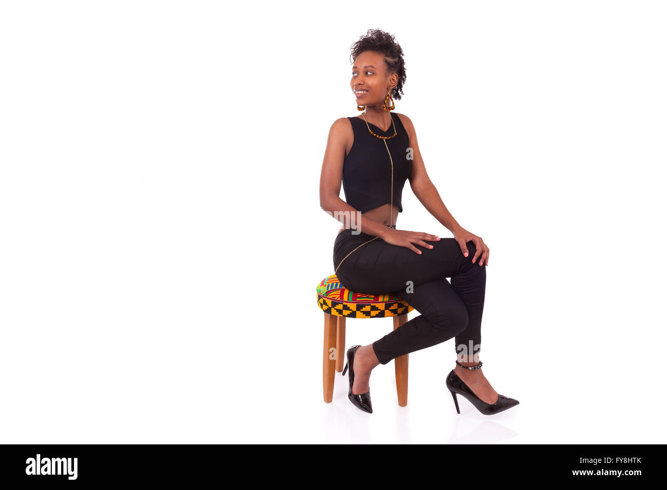 Beautiful African American woman sitting on a stool isolated on white background - Stock Image