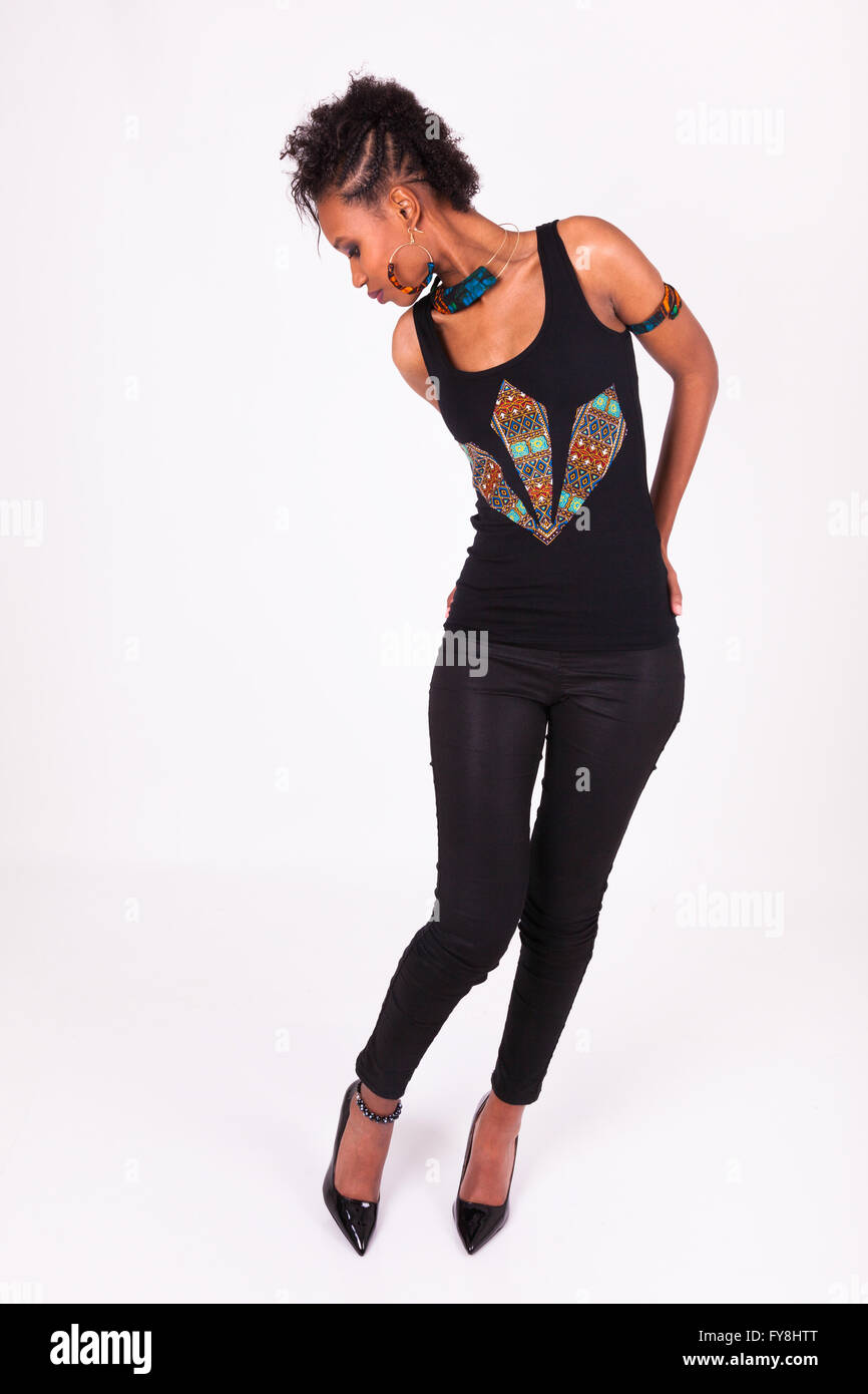 Beautiful African American woman with curly hairs looking to her high heels - Stock Image