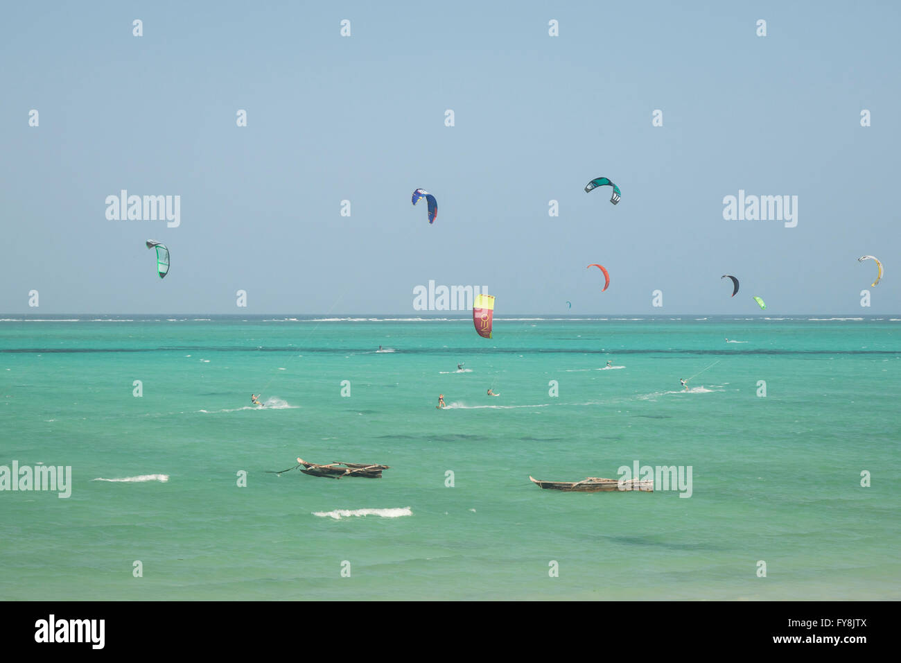 Kitesurfers kiting near wooden fish boats in the Indian ocean at Tanzania, Zanzibar - Stock Image