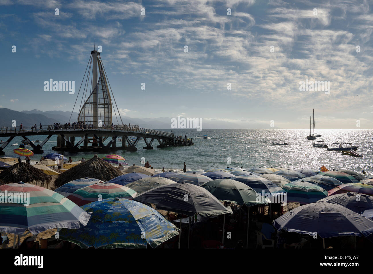 Beach umbrellas on Los Muertos beach at the Pier and Sierra Madre mountains Puerto Vallarta Mexico - Stock Image