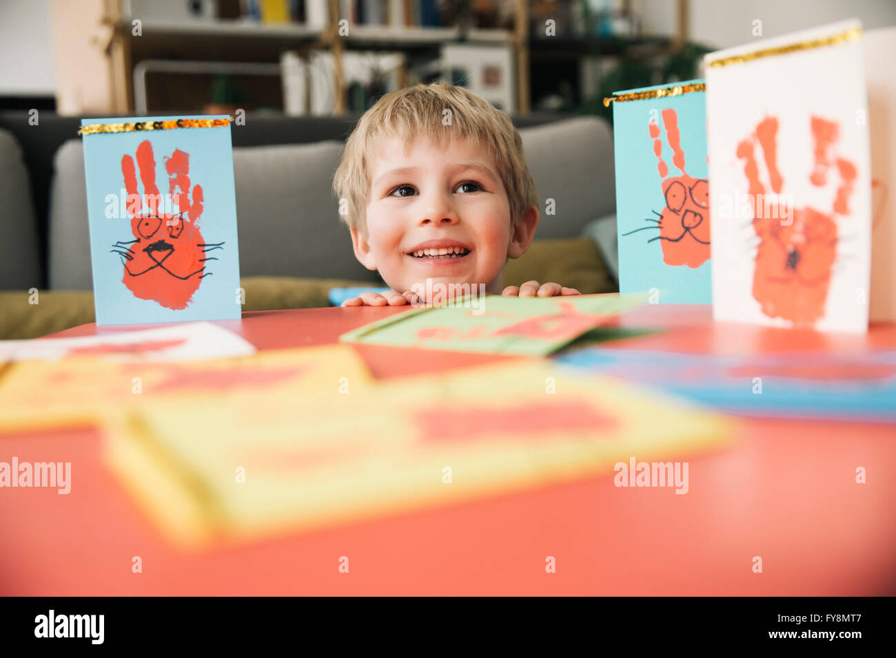 Happy little boy with self-made Easter cards at home - Stock Image