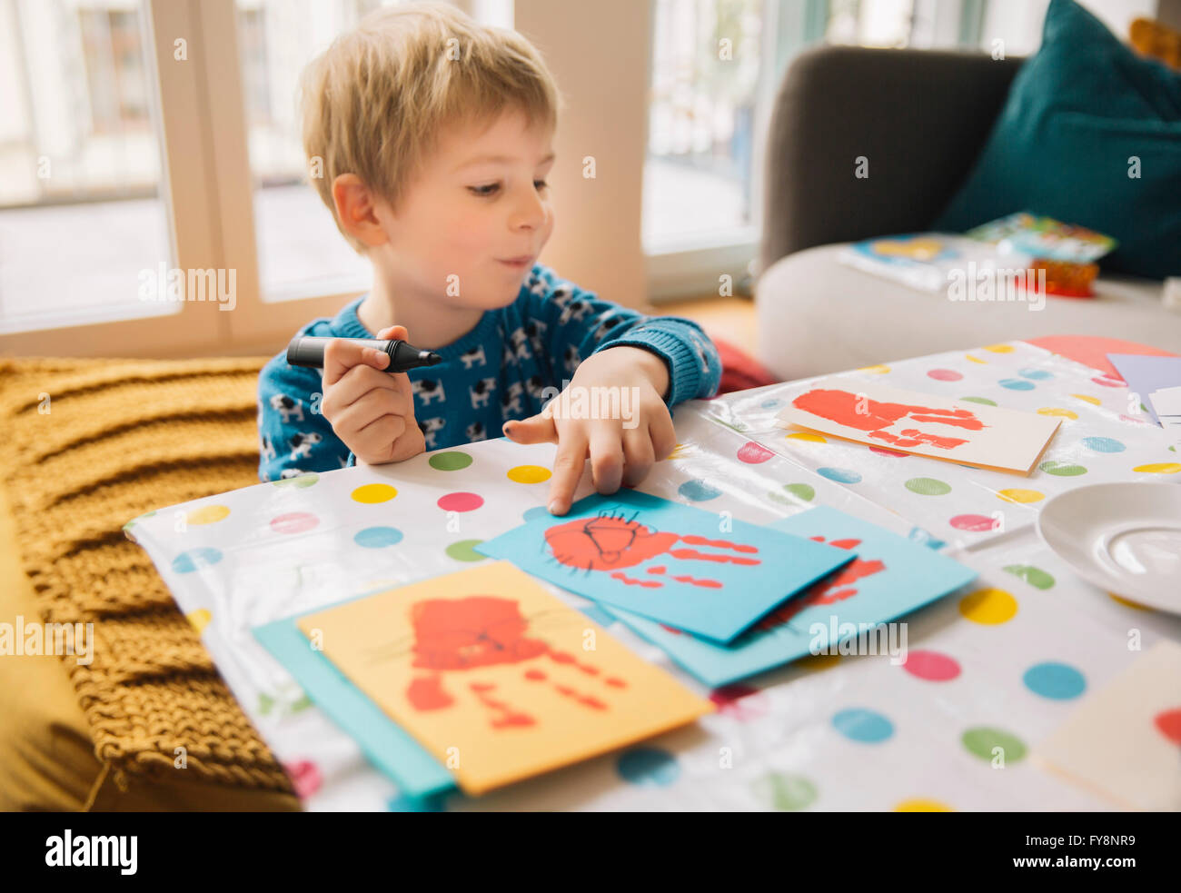 Little boy creating Easter cards with handprints at home - Stock Image
