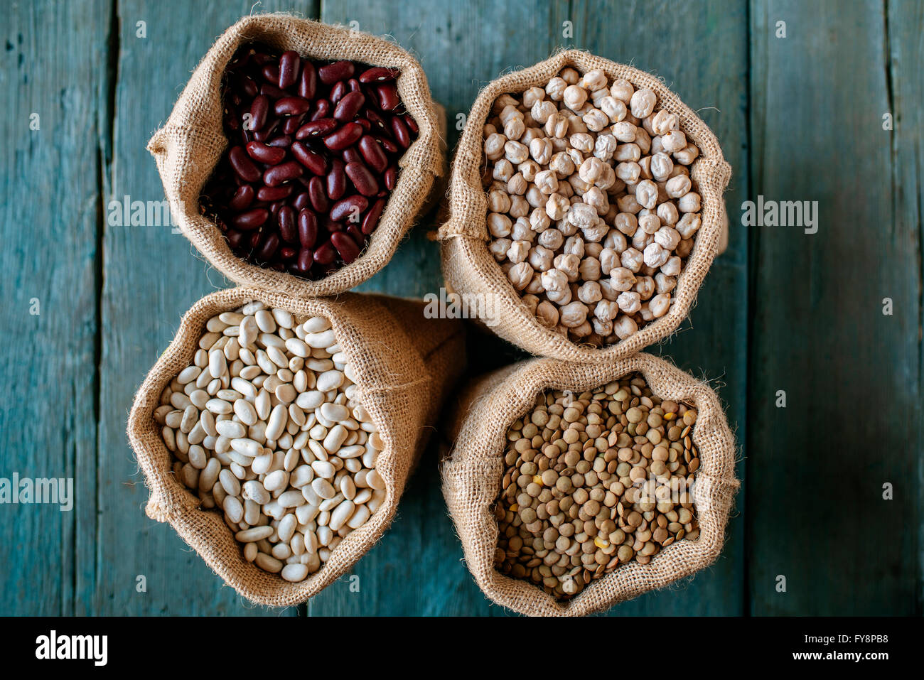 Four sacks of dried brown lentils, chickpeas and red and white beans on wood - Stock Image