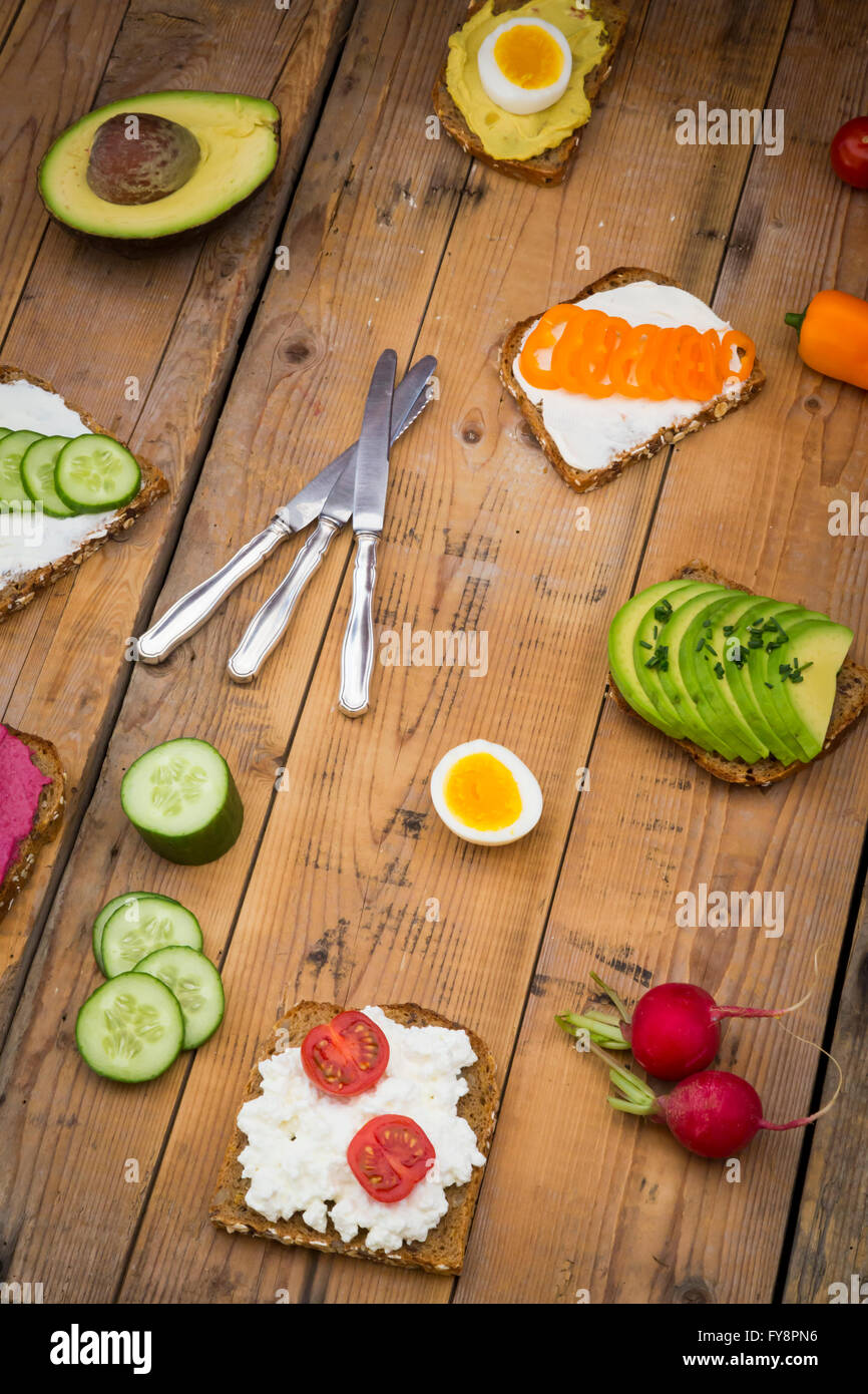 Wholemeal bread slices with different spreads and toppings on wood - Stock Image